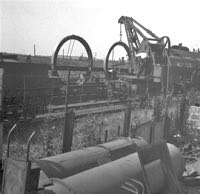 Castings, having been lifted over boundary fence, being loaded by  railway personnel